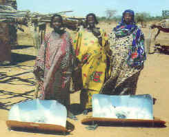 three refugee women proudly display their solar cookers.