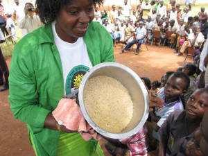 Children look on with awe as Olivia Kanyesigye reveals a pot of solar-cooked rice