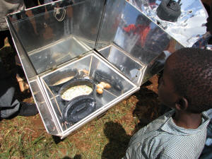 A child from Nairobi�s Kangemi slum looks on as SCI solar cooks an omelet, his first lunch in many months