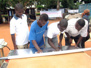Operation Amis du Soleil participants start the solar cooker construction process by adhering reflective foil to cardboard