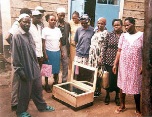 Henry Ogola Oloo (left) explains solar cooking to a cultural group in Kiberia, Kenya