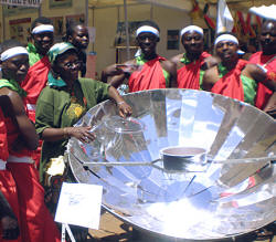 SCI's Faustine Odaba explains solar cooking to a group of dancers.