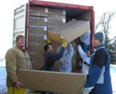 Five South Dakota State University football players volunteered to load the sea container with 1000 unassembled solar box cookers destined for Haiti